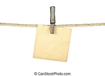 Old wooden clothespin on rope with old paper