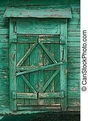 Old wooden country window with closed shutters painted green