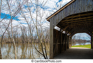 old wooden covered bridge by river