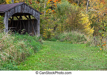 old wooden covered bridge in autumn