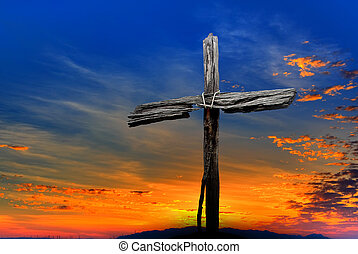 Old wooden cross over dramatic sunset