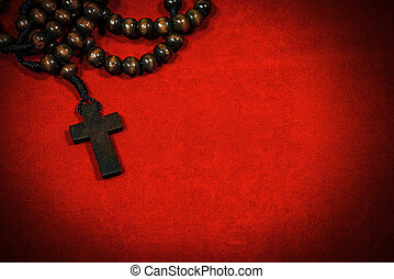 Old Wooden Crucifix with Rosary Beads on Red Velvet Background