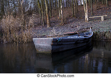 Old wooden dinghy moored to the shore of a lake
