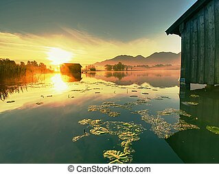 Old wooden dock houses on the lake with typical wooden pier,