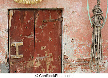 Old wooden door and a pink wall