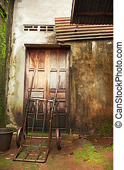 Old wooden door and wall of a house damaged by moisture