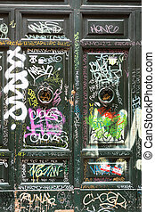 Old wooden door covered with graffiti in Trastevere...