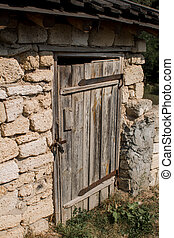 old wooden door in a stone wall locked