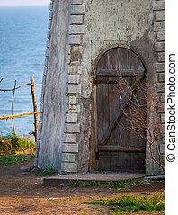 Old wooden door in brick wall in monastery on sea coast