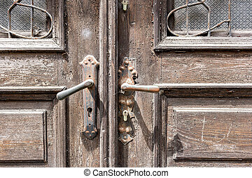 Old wooden door of a shabby demaged house facade. A small town in the mountains of Slovenia, Europe.