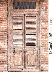 Old wooden door on brick wall.