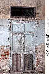 Old wooden door on wall of house