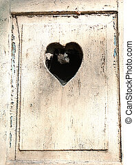 old wooden door with a carved romantic heart - old wooden...