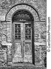 Old wooden door with brick archway.