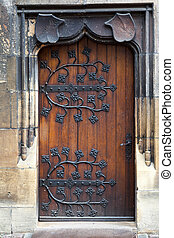 old wooden door with decorative, forged metal hinges