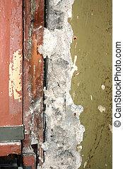 Old wooden door with locks. Broken wall near the door. Repair in the apartment.