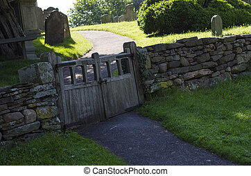 Old wooden double gate in dry stone wall to churchyard