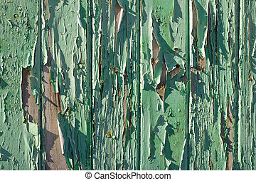 Old wooden fence flaky green paint close up.