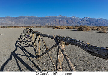 Old wooden fence in desert by mountains