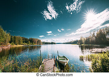 Old Wooden Fishing Boat Moored Near Pier In Summer Lake Or River. Beautiful Summer Sunny Day Or Evening. Swedish Nature. Arjang SV, Tocksfors, Sweden