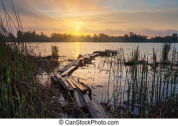 Old wooden fishing pier at sunrise