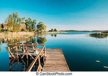 Old Wooden Fishing Pier Near Summer Lake Or River. Calm Water In Beautiful Summer Sunny Day.