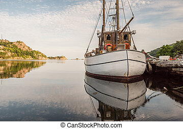 Old wooden fishingboat docked. Calm water