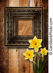 Old wooden frame for photo with bunch of flower narcissus
