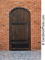 Old wooden gates and walls of red brick.