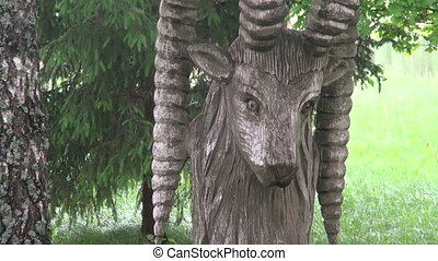 old wooden goat sculpture and bench