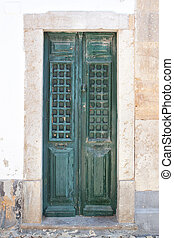 Old wooden green doors on the streets of Portugal.
