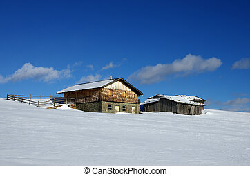 old wooden hat on the alps in winter