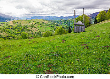 old wooden hay shed on grassy hillside. beautiful scenery of...