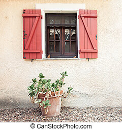 Old wooden home window with open shutters and tropical plant in flower pot