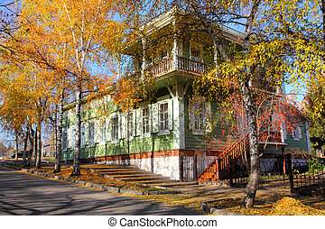 old wooden house between autumn trees in Ufa Russia