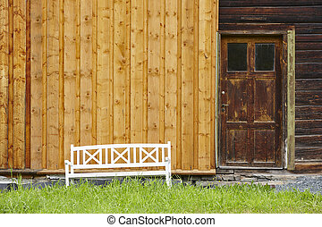 Old wooden house facade with bench and green plants.
