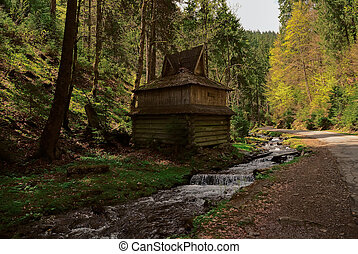 Old wooden house in the forest near the river and forest against the blue sky