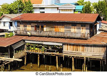 Old wooden houses beside the Chao Phraya River. Bangkok, Thailand.