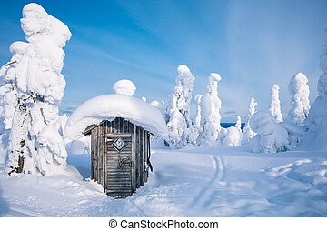 Old wooden hut in winter snowy forest in Finland, Lapland.