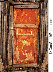 Old wooden orange door with a rusty lock