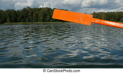 Old wooden paddle bounces into lake water. - Old wooden...