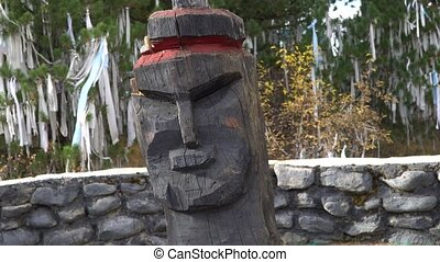Old wooden pagan idol head on ritual ribbons sacred tree background in the Altai Mountains. Slide shot.