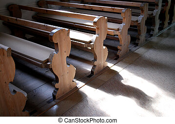 old wooden pews in a bavarian church with light an shadow