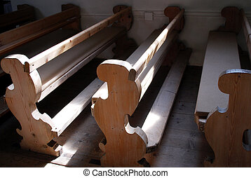 old wooden pews in a bavarian rural chapel with light and shadow