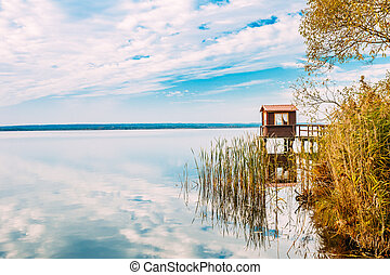 Old Wooden Pier For Fishing, Small House Or Shed And Beautiful Lake