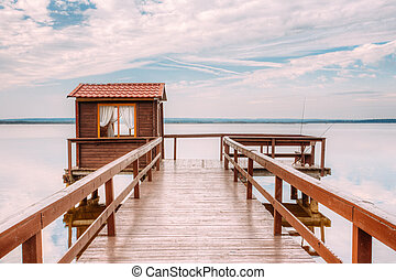 Old wooden pier for fishing, small house shed and beautiful lake or river