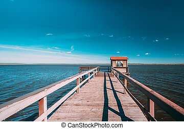Wooden Pier For Fishing, Small House Shed And Beautiful Lake Or River In Background. Picturesque Natural Landscape In Berezinsky, Biosphere Reserve, Belarus