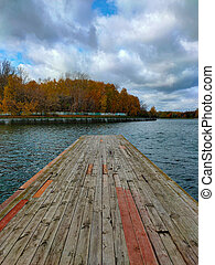 Old wooden pier in lake. Autumn park.