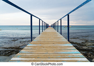 Old wooden pier leading to the sea on Cyprus.