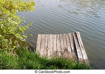 Old wooden pier on a lake at sunny summer day.